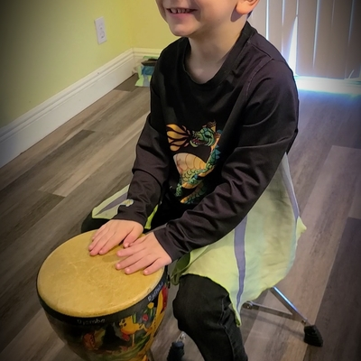 Kael drumming and singing in the play