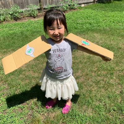 Posing with her cardboard arms like an airplane wing!
