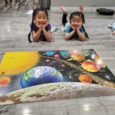 Joy and Faith put together a puzzle after learning about the planets